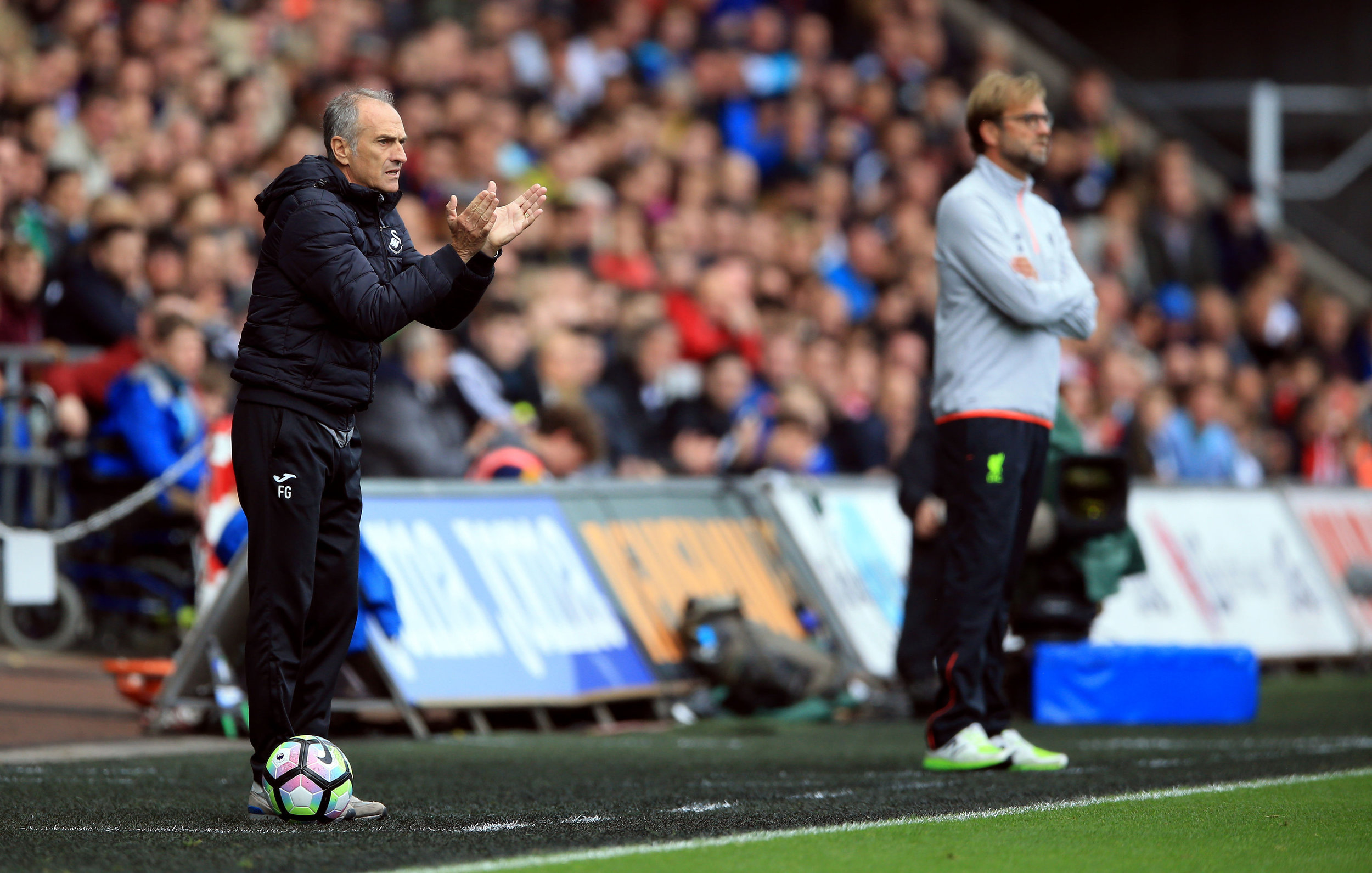 Swansea City manager Francesco Guidolin encourages his players, with Liverpool's manager Jurgen Klopp, right, during their English Premier League soccer match at the Liberty Stadium, Swansea, England, Saturday Oct. 1, 2016. (Nigel French / PA via AP)