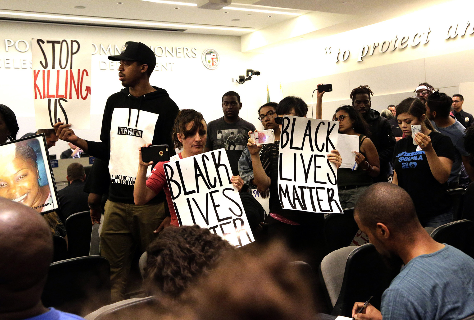 Black Lives Matter protesters demonstrate inside the board of Police Commissioners meeting in Los Angeles on Tuesday, Oct. 4, 2016. Los Angeles police released surveillance video Tuesday showing an 18-year-oldblack suspect running from police while holding what appears to be a gun in his left hand just before he was fatally shot by officers in a death that has generated rowdy protests. (Nick Ut/AP)