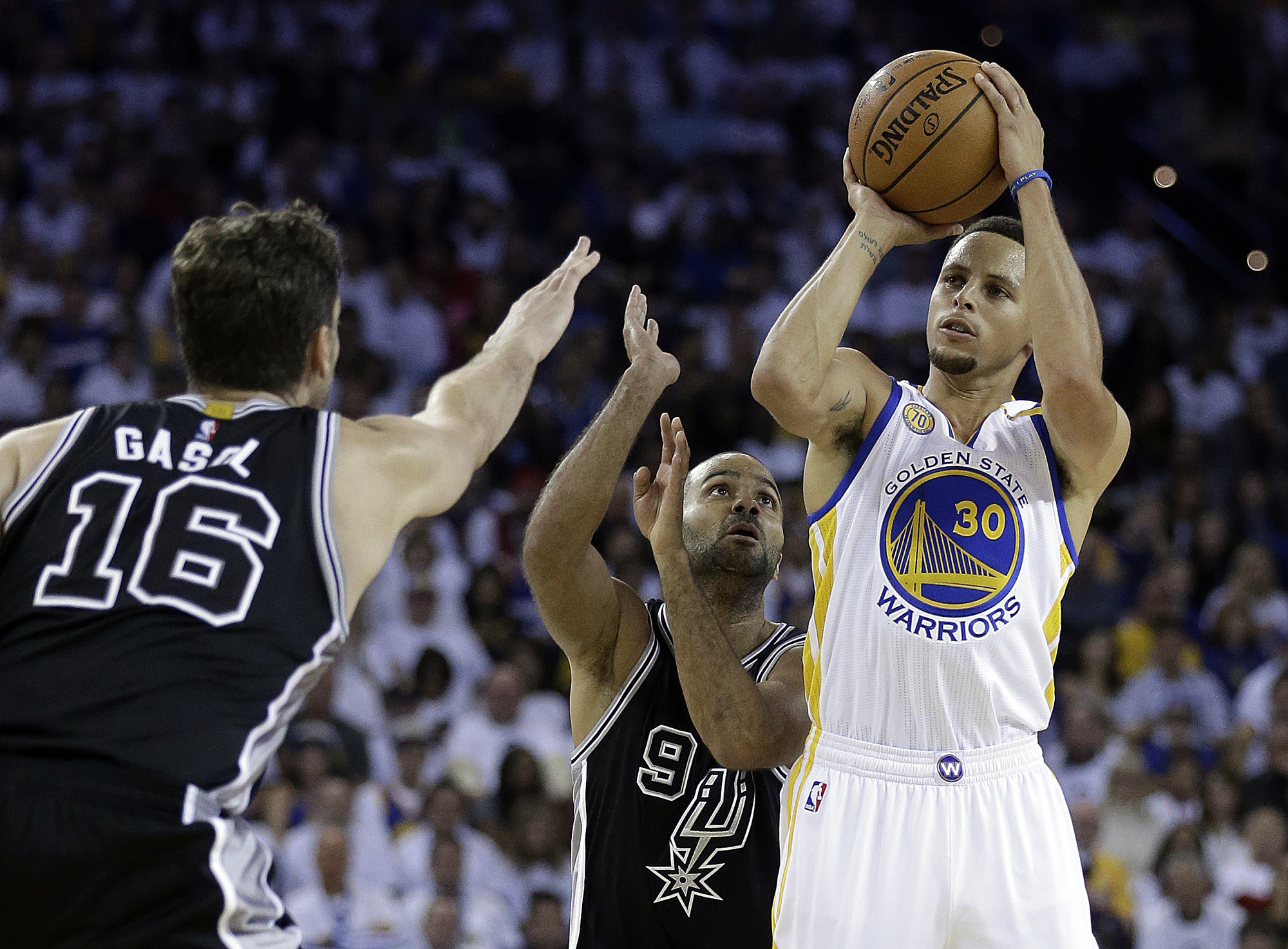 Golden State Warriors' Stephen Curry, right, shoots against San Antonio Spurs' Tony Parker (9) and Pau Gasol (16) during the first half of an NBA basketball game Tuesday, Oct. 25, 2016, in Oakland, Calif. (Ben Margot/AP)