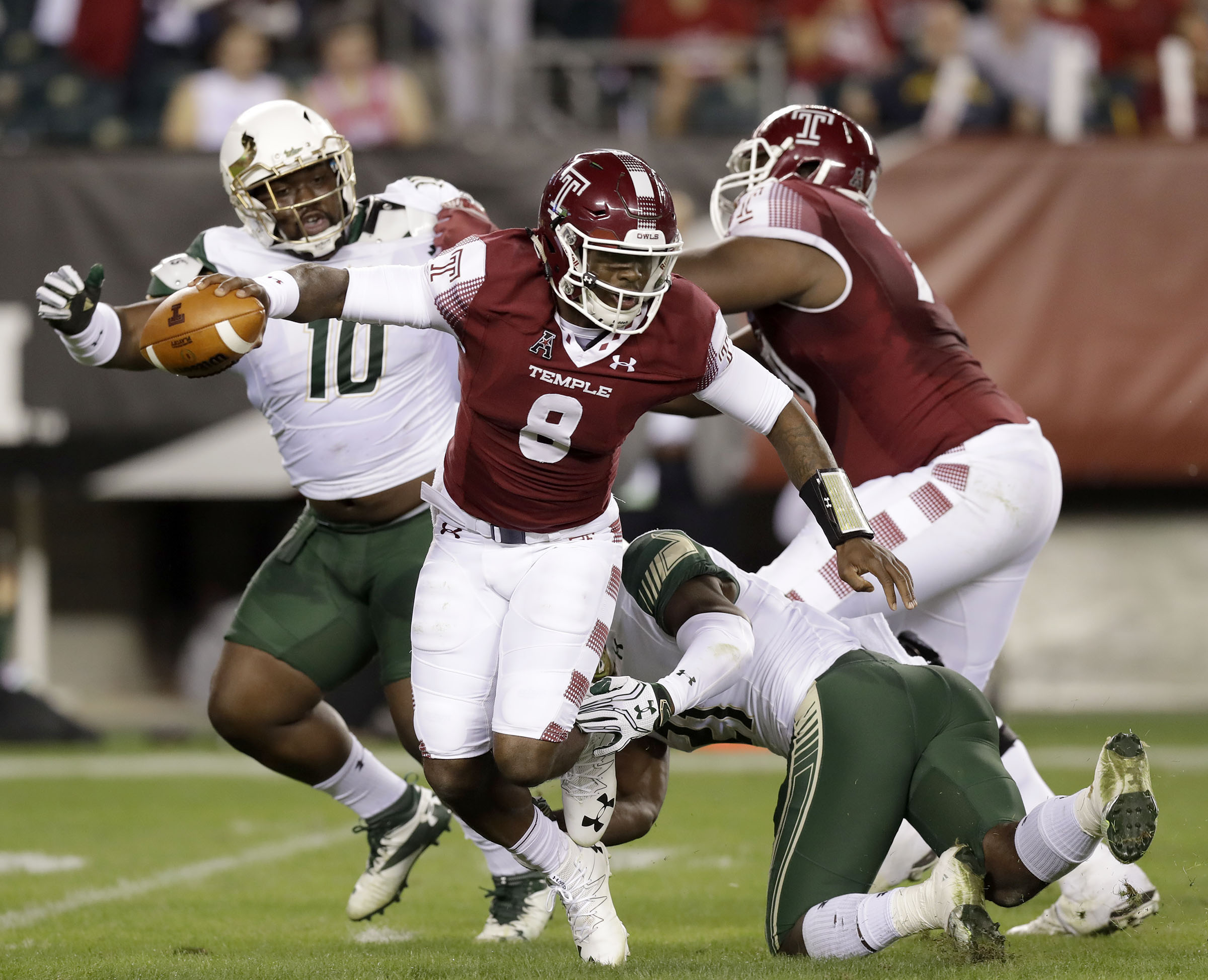 Temple quarterback Phillip Walker escapea from South Florida's Khalid McGee as Deadrin Senat, left, gets blocked by Temple offensive lineman Jovahn Fair during the first quarter of an NCAA college football game Friday, Oct. 21, 2016, in Philadelphia. (Yong Kim/The Philadelphia Inquirer via AP)