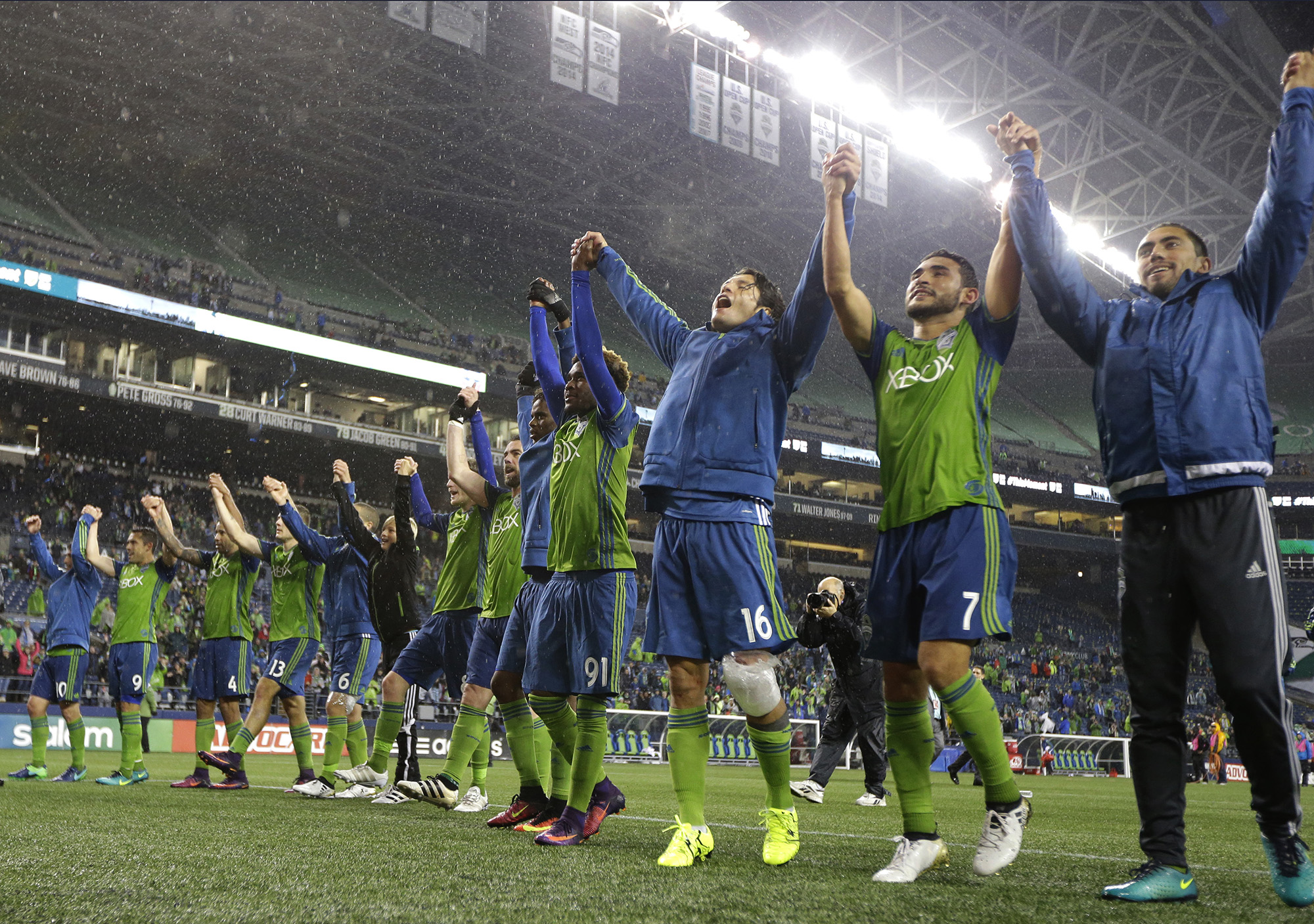 Seattle Sounders players, including Cristian Roldan (7) and Nelson Haedo Valdez (16) celebrate after they beat FC Dallas 3-0 in an MLS soccer playoff match, Sunday, Oct. 30, 2016, in Seattle. (Ted S. Warren/AP)