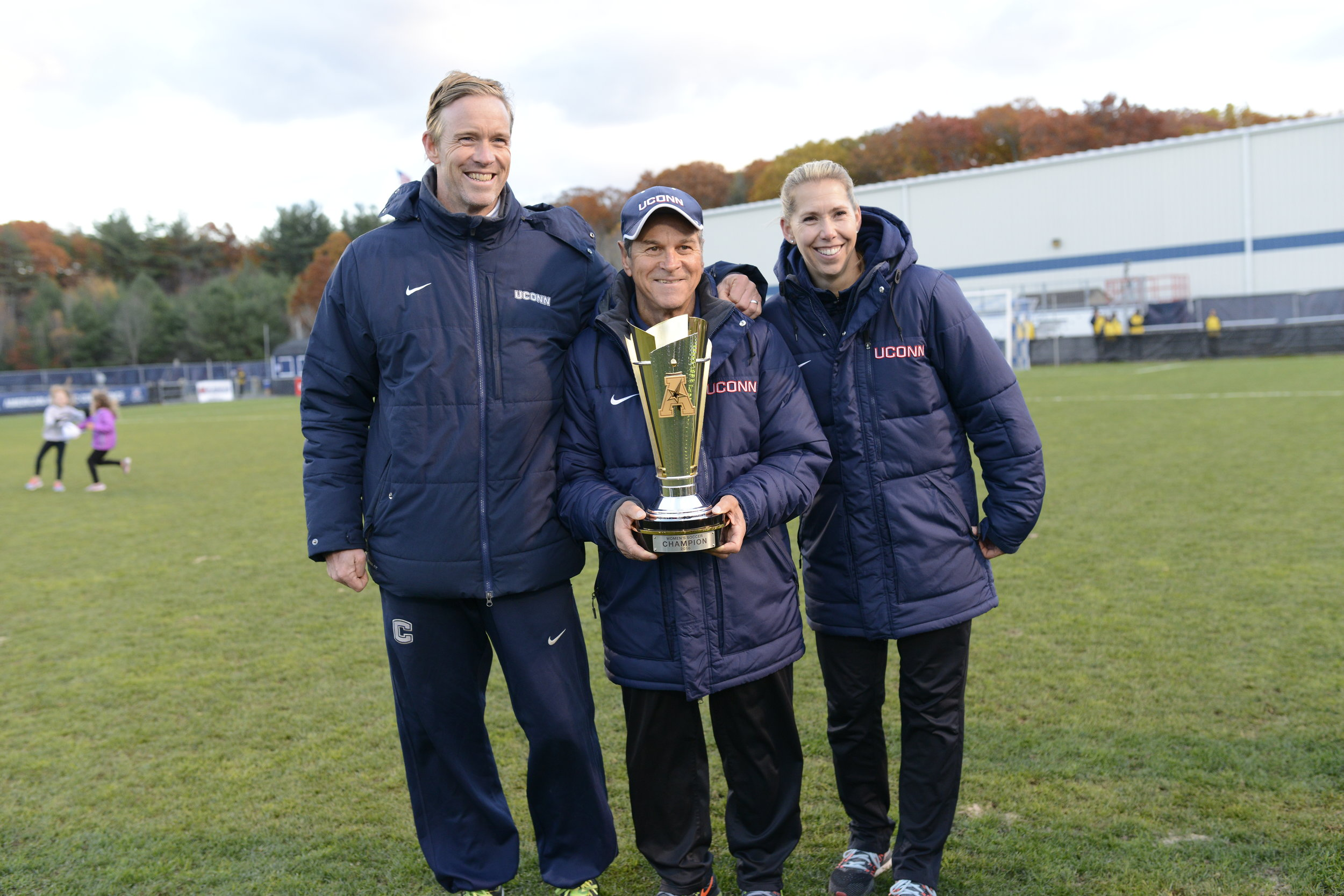 From left to right: Associate head coach Zac Shaw, head coach Len Tsantiris and associate head coach Margaret Rodriguez pose with the American Athletic Conference championship trophy following a 1-0 win over SMU on Sunday, Nov. 6 at Joseph J. Morrone Stadium. Tsantiris was named AAC co-coach of the year, sharing the honors with SMU's head coach. (Jason Jiang/The Daily Campus)