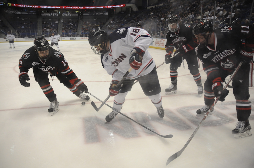 UConn's Max Kalter (#18) battles for the puck while surrounded by Northeastern players during UConn's loss Friday night. (Angie DeRosa/The Daily Campus)