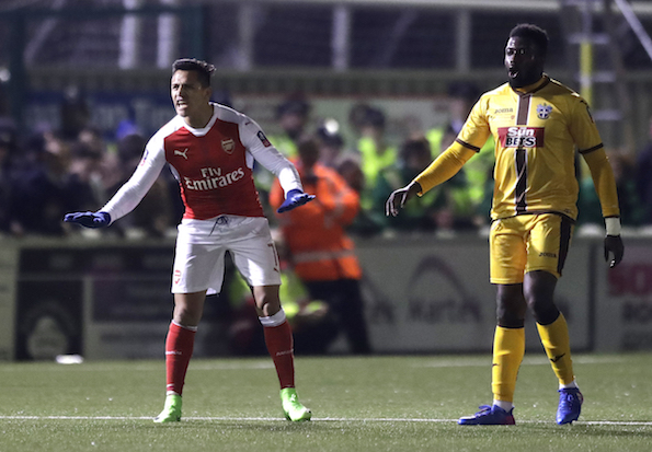 Arsenal's Alexis Sanchez, left, gestures to his teammates during the English FA Cup fifth round soccer match between Arsenal and Sutton United at Gander Green Lane stadium in London, Monday, Feb. 20, 2017. (AP Photo/Matt Dunham)