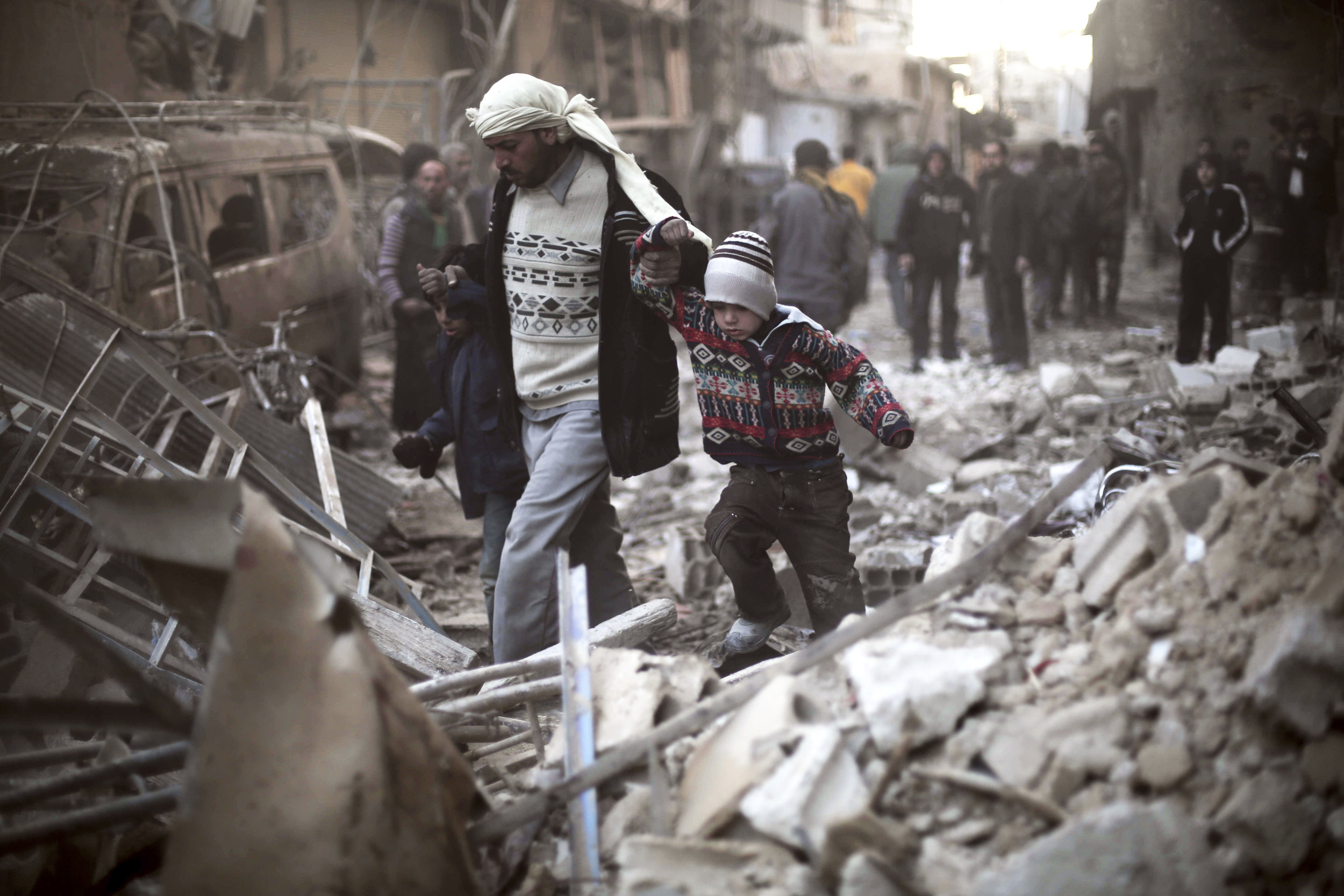 This Dec. 24, 2015 file photo provided by Save the Children, a man walks with a pair of children in hand hand through the rubble in Eastern Ghouta, Syria. (Save the Children via AP, File)