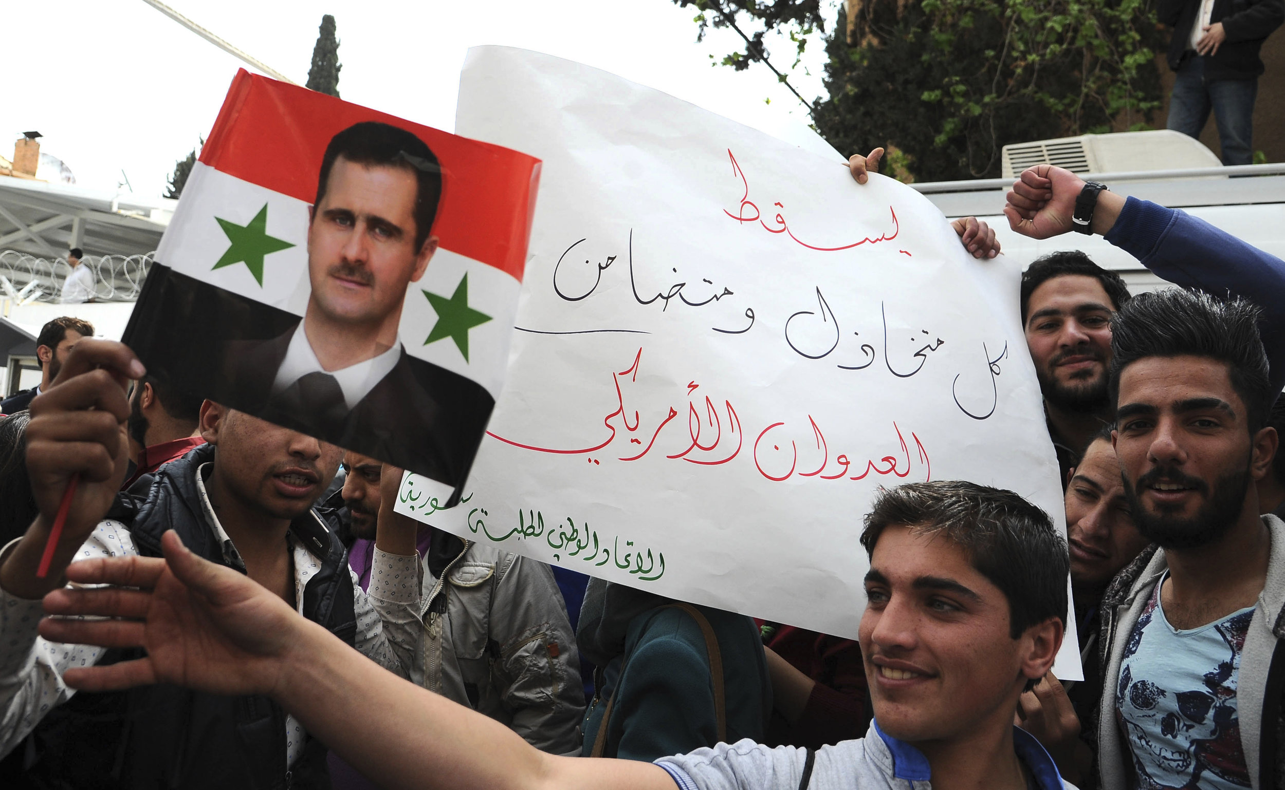 "In this photo released by the Syrian official news agency SANA, pro-government protesters hold a portrait of President Bashar Assad and a placard that reads, ""Down with everyone who cooperated and supported the American aggression,"" during a protest in front of the the United Nations building, in Damascus, Syria, Tuesday, April 11, 2017.  (SANA via AP)"