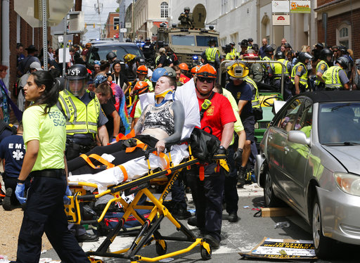 In this Aug. 12, 2017 file photo, rescue personnel help injured people who were hit when a car ran into a large group of protesters after a white nationalist rally in Charlottesville, Va.(AP Photo/Steve Helber, File)
