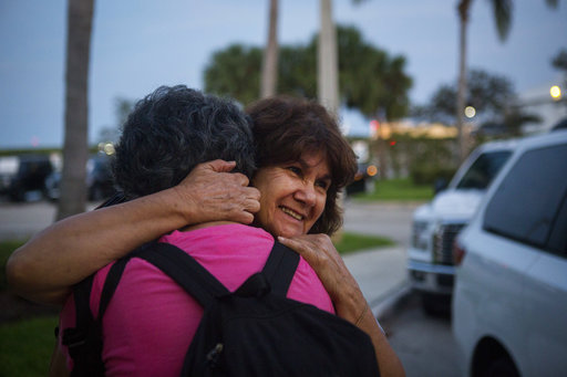 Martha Roman of Tampa is reunited with her sister Millie Fernandez after she arrived in West Palm Beach, Fla., from Puerto Rico on Tuesday, Sep. 26, 2017.(Calla Kessler/Palm Beach Post via AP)