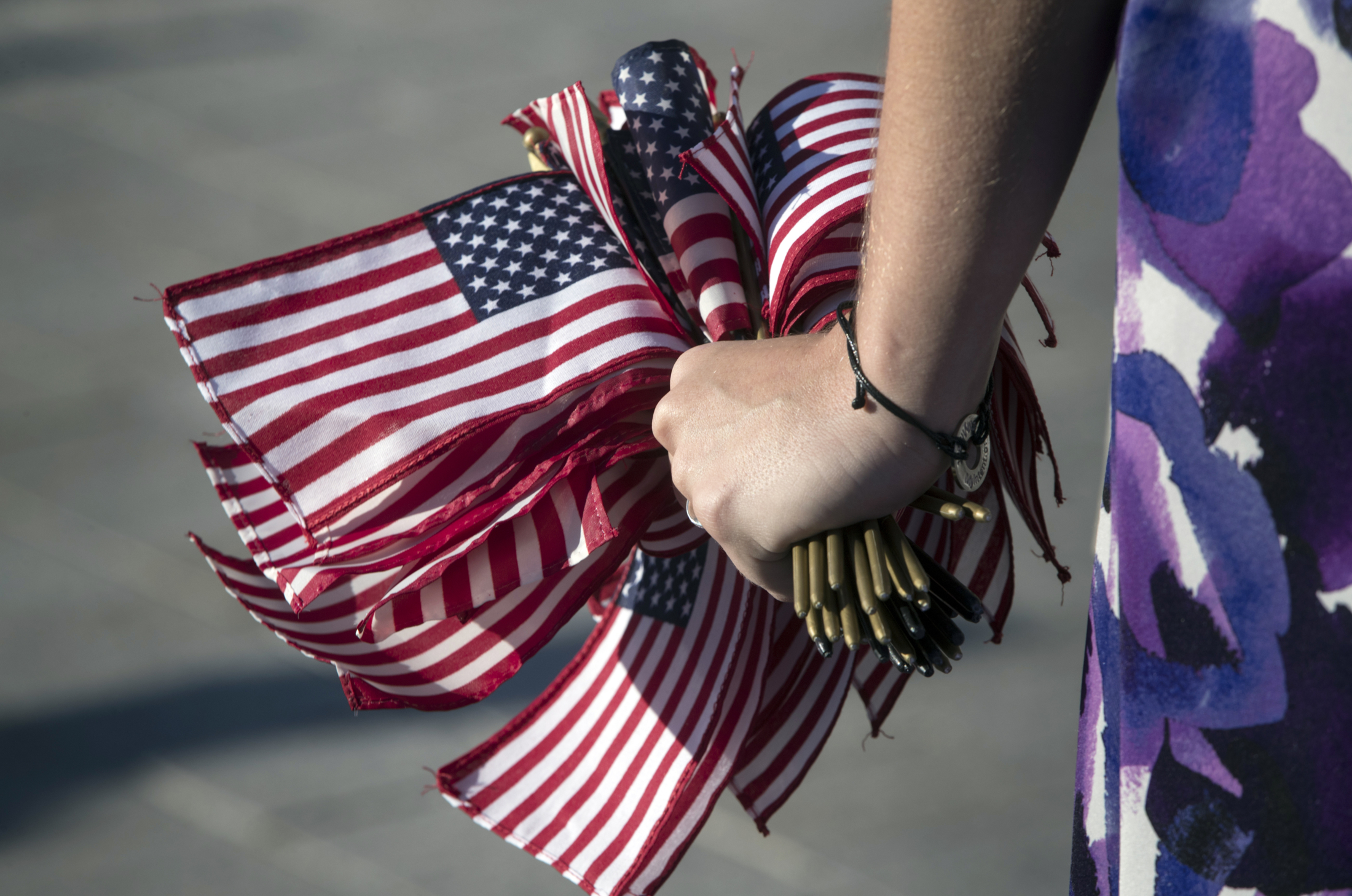 A congressional staffer holds a handful of small American flags to pass out as Democratic members of the House of Representatives rally for action on gun safety legislation after the deadly mass shooting in Las Vegas this week, at the Capitol in Washington, Wednesday, Oct. 4, 2017. (J. Scott Applewhite/AP)