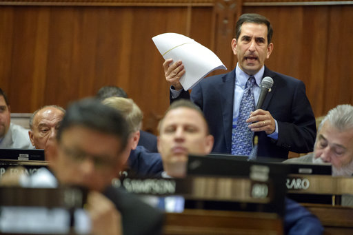 State Rep. Doug Dubinsky holds a copy of the 881-page budget bill and speaks about the lack of time to read it before a vote, Thursday, Oct. 26, 2017 at the Statehouse in Hartford, Conn. The budget bill went on to pass 126-23. (Mark Mirko/The Courant via AP)