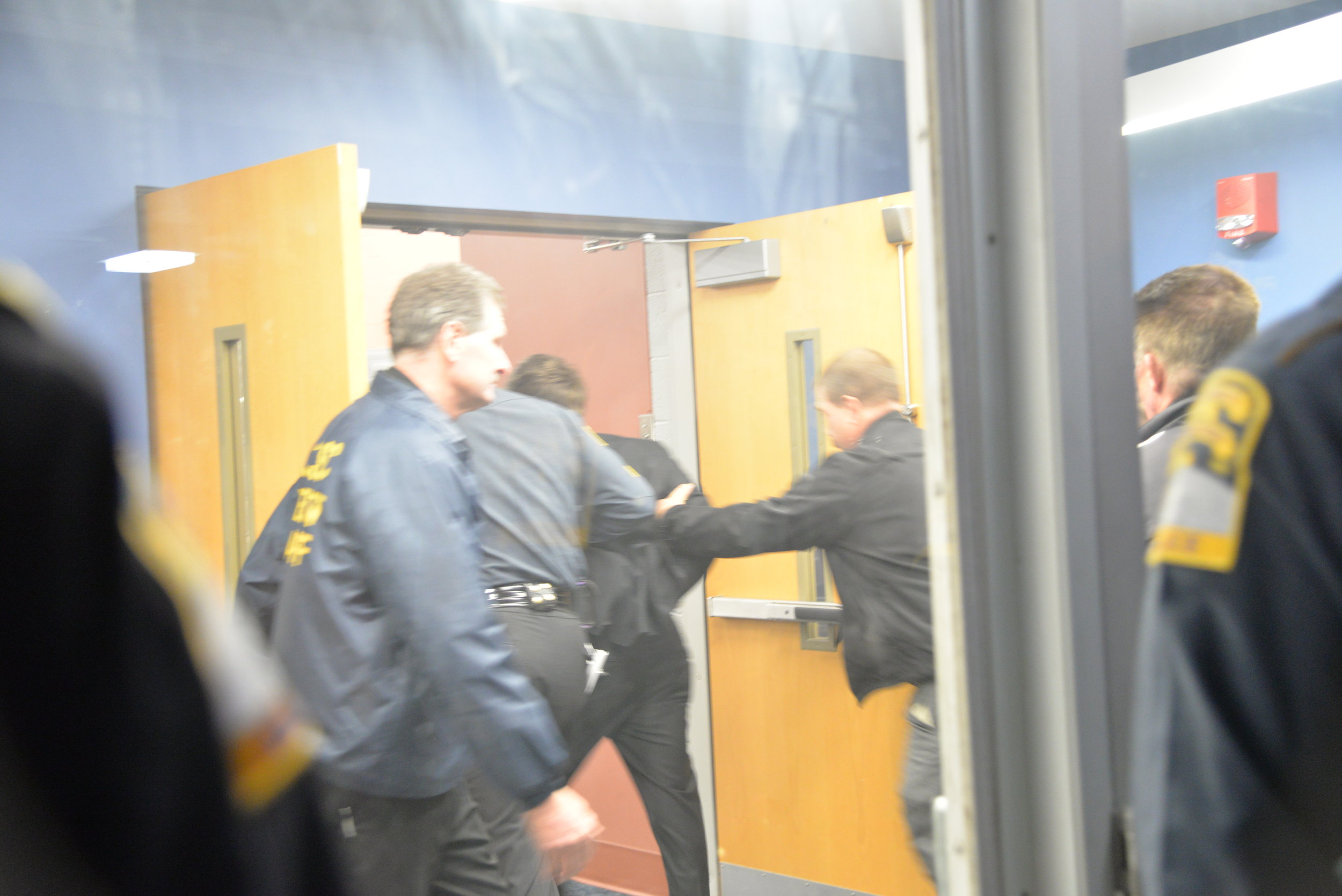 Wintrich was escorted through the back door of Schenker Hall. He was charged with second degree breach of peace. (Amar Batra/The Daily Campus)