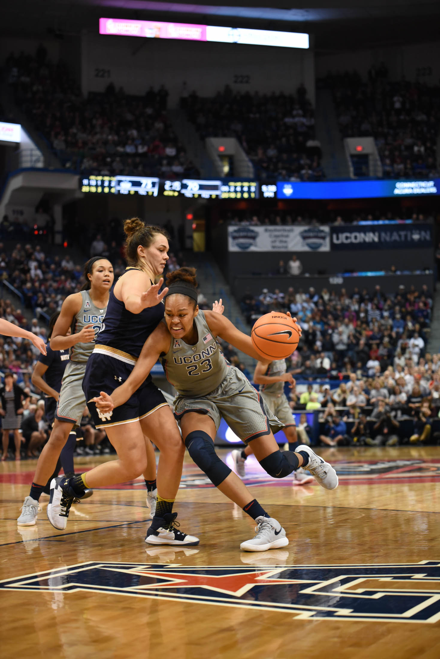 Azura Stevens drives down the lane to pass a guard. She finishes the game with 17 points. (Charlotte Lao/The Daily Campus)