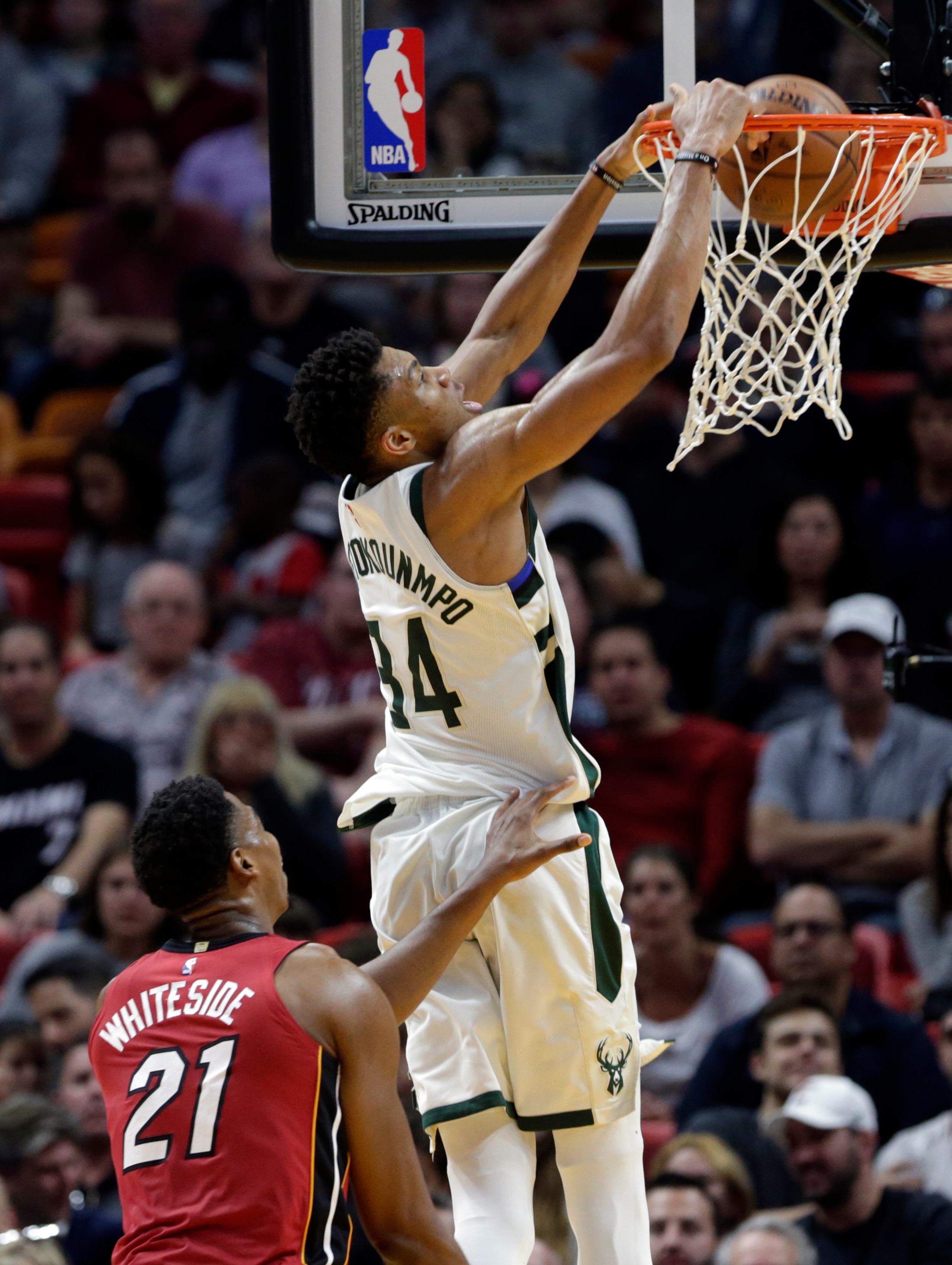Milwaukee Bucks' Giannis Antetokounmpo (34) dunks over Miami Heat's Hassan Whiteside (21) during the second half of an NBA basketball game, Sunday, Jan. 14, 2018, in Miami. (AP Photo/Lynne Sladky)