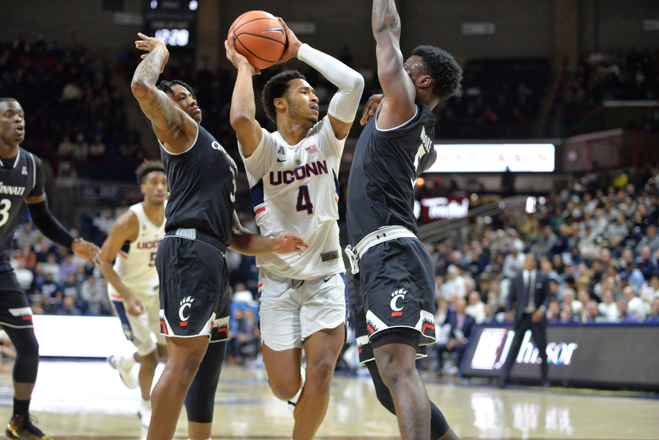 Junior guard Jalen Adams (4) fights off Cincinnati defenders during the Huskies 65-57 loss to the Bearcats in Gampel Pavilion on Saturday, Feb. 3, 2018. Adams leads the team in points and assists. (Amar Batra/The Daily Campus)