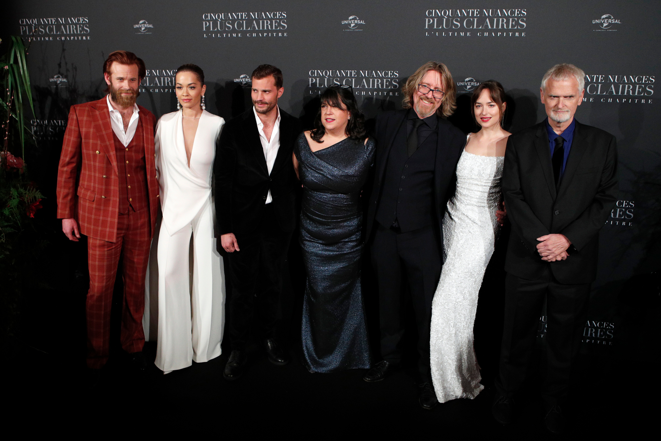 From left to right, Eric Johnson, Rita Ora, Jamie Dornan, E.L. James, a guest, Dakota Johnson, and James Foley pose during a photocall for the world premiere of 'Fifty Shades Freed - 50 Nuances Plus Claires' at Salle Pleyel in Paris, Tuesday, Feb. 6, 2018. (AP Photo/Francois Mori)