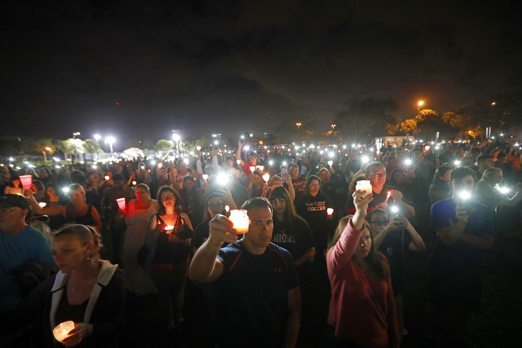 People participate in a candlelight vigil in memory of the 17 students and faculty who were killed in the Wednesday mass shooting at Marjory Stoneman Douglas High School in Parkland, Fla., Monday, Feb. 19, 2018. Nikolas Cruz, a former student, was charged with 17 counts of premeditated murder on Thursday. (Gerald Herbert/AP)
