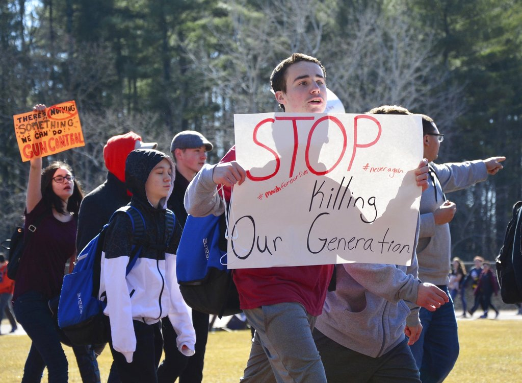 Taconic High School students march around the running track during a rally at the school's athletic field in Pittsfield, Mass. on Tuesday, Feb. 27, 2018. Students in the Pittsfield school system walked out of class in solidarity with victims of the recent mass shooting in Parkland, Fla. (Gillian Jones/The Berkshire Eagle via AP)