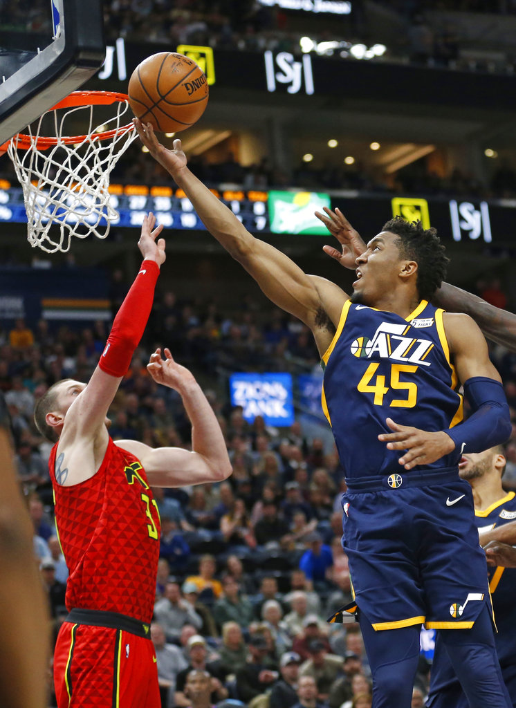 Utah Jazz guard Donovan Mitchell (45) lays the ball up as Atlanta Hawks forward Mike Muscala (31) defends during the second half of an NBA basketball game Tuesday, March 20, 2018, in Salt Lake City. (AP Photo/Rick Bowmer)
