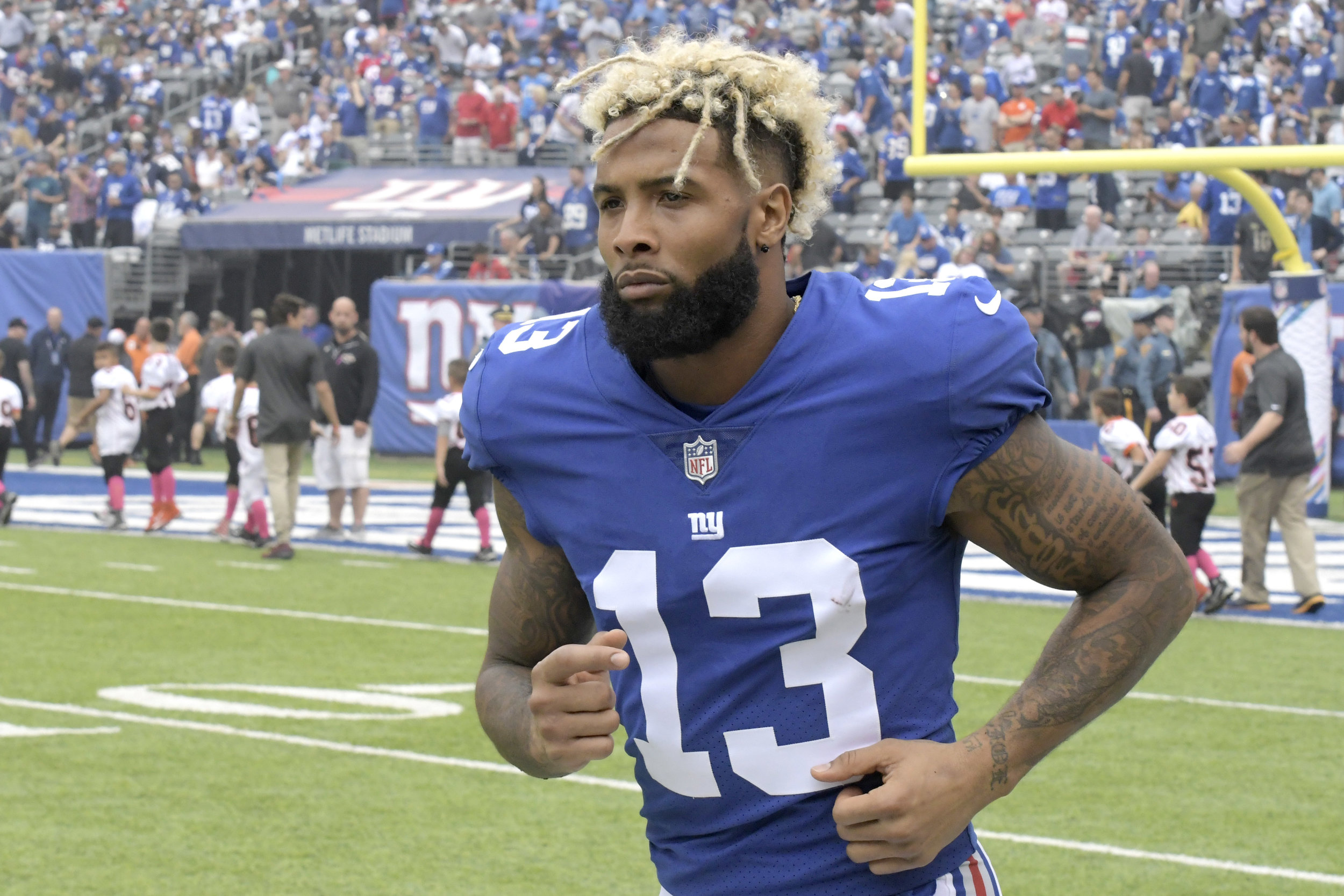 "FILE - In this Oct. 8, 2017, file photo, New York Giants wide receiver Odell Beckham warms up prior to an NFL football game against the Los Angeles Chargers, in East Rutherford, N.J. Giants coach Pat Shurmur says he expects Odell Beckham Jr. to attend offseason workouts when they start in April. Trade rumors are surrounding the controversial star receiver and there has been strong speculation Beckham will hold out during training camp because he doesn't want to play the fifth and final year of his rookie deal without a new contract. ""All reports are he will be ready to go as we get going,"" Shurmur said Tuesday morning, March 27, 2018, at the NFL meetings. (AP Photo/Bill Kostroun, File)"