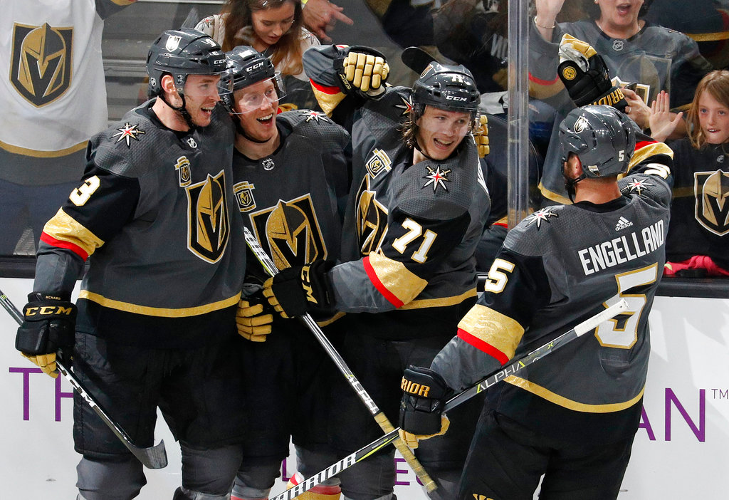 FILE - In this March 31, 2018, file photo, Vegas Golden Knights players celebrate after center William Karlsson (71) scored against the San Jose Sharks during the third period of an NHL hockey game in Las Vegas. The NHL-expansion Golden Knights carry the buzz entering the Western Conference playoffs, which have the potential of resembling nothing from the past. (AP Photo/John Locher, File