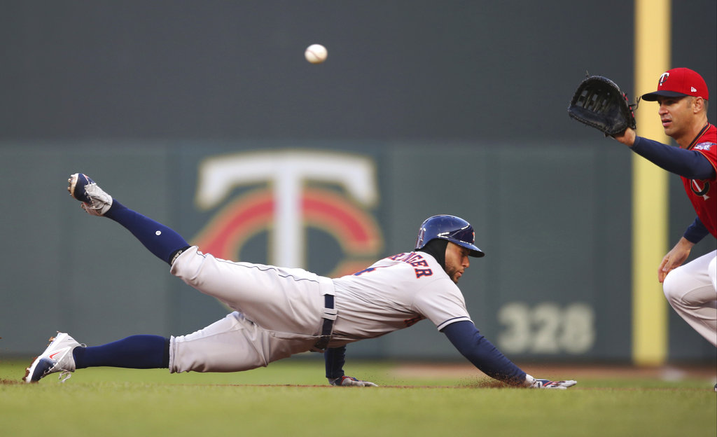 Houston Astros' George Springer dives safely back to first base as Minnesota Twins first baseman Joe Mauer waits for the throw during the first inning of a baseball game Tuesday, April 10, 2018, in Minneapolis. (AP Photo/Jim Mone)