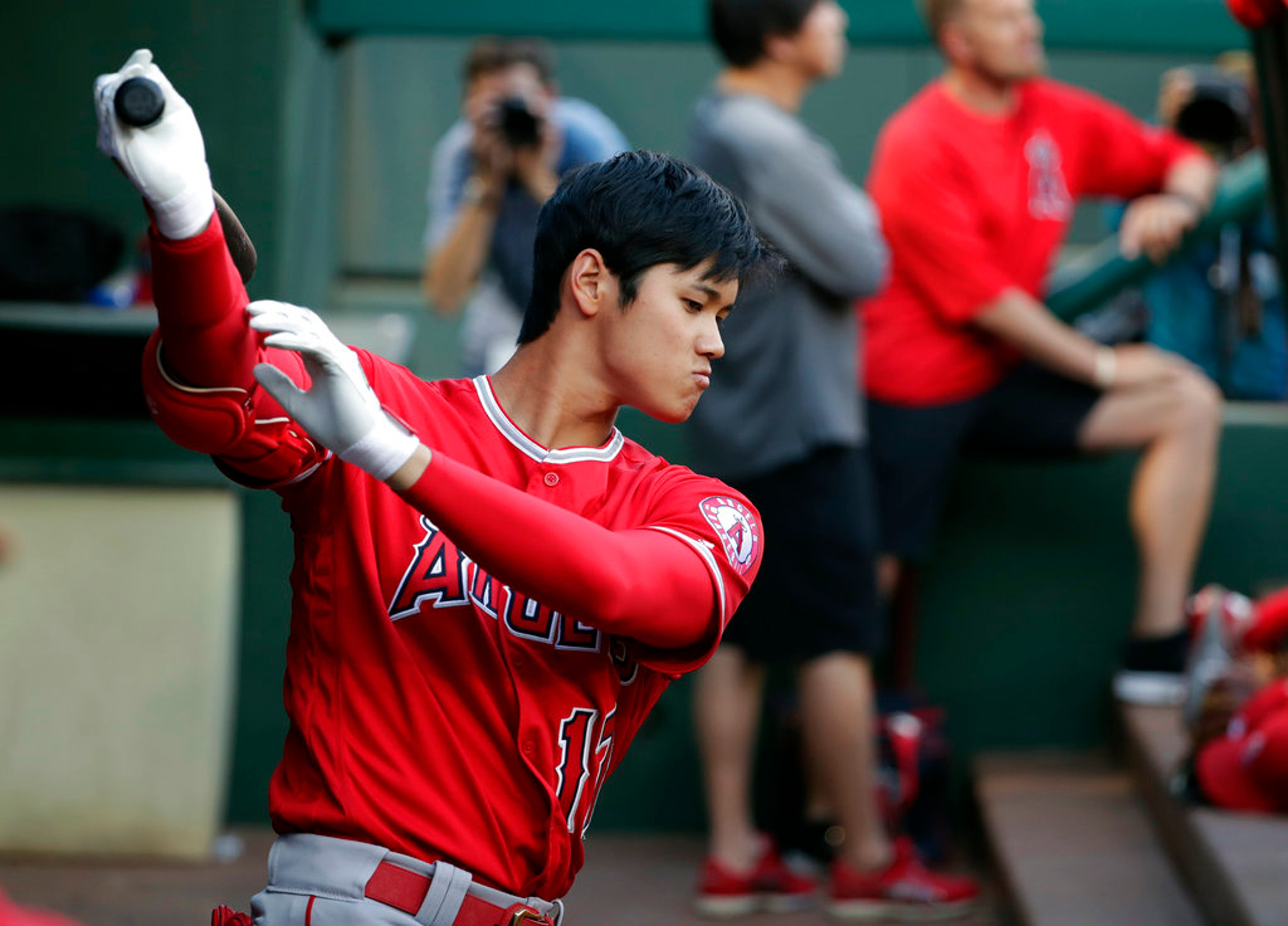 FILE - In this April 11, 2018, file photo, Los Angeles Angels' Shohei Ohtani takes a practice swing in the dugout in the first inning of a baseball game against the Texas Rangers in Arlington, Texas. Ohtani eagerly bounces into the cage when it's his turn in batting practice _ and then puts on an impressive show. The rookie two-way sensation is always ready to go, whether hitting or pitching for the Angels. (AP Photo/Tony Gutierrez, File)