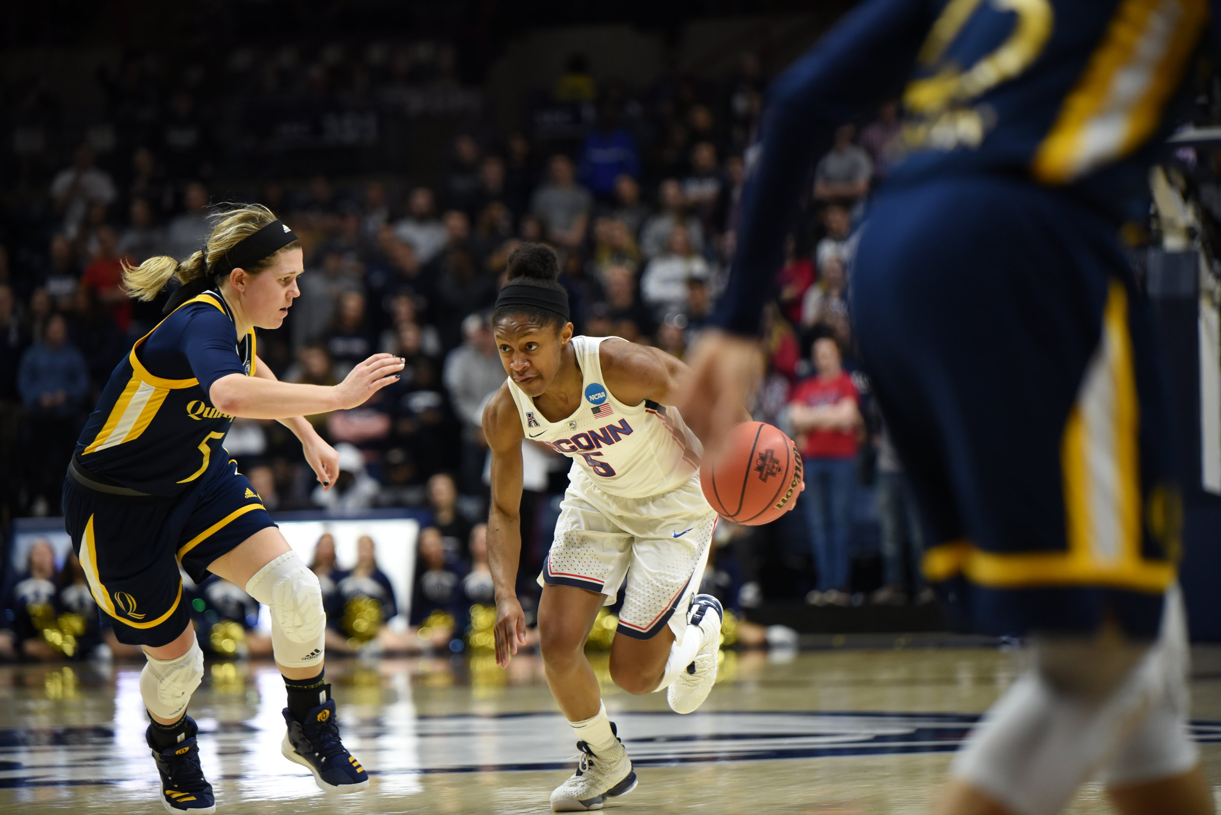 Crystal Dangerfield pushes the ball up the court. (Charlotte Lao/The Daily Campus)