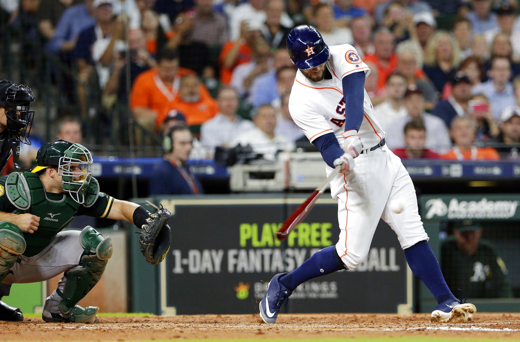 Houston Astros' George Springer, right, connects for an RBI single with bases loaded in front of Oakland Athletics catcher Josh Phegley, and umpire Mark Weiner, left, making the score 4-3 during the fourth inning of a baseball game Wednesday, Aug. 29, 2018, in Houston. (AP Photo/Michael Wyke)