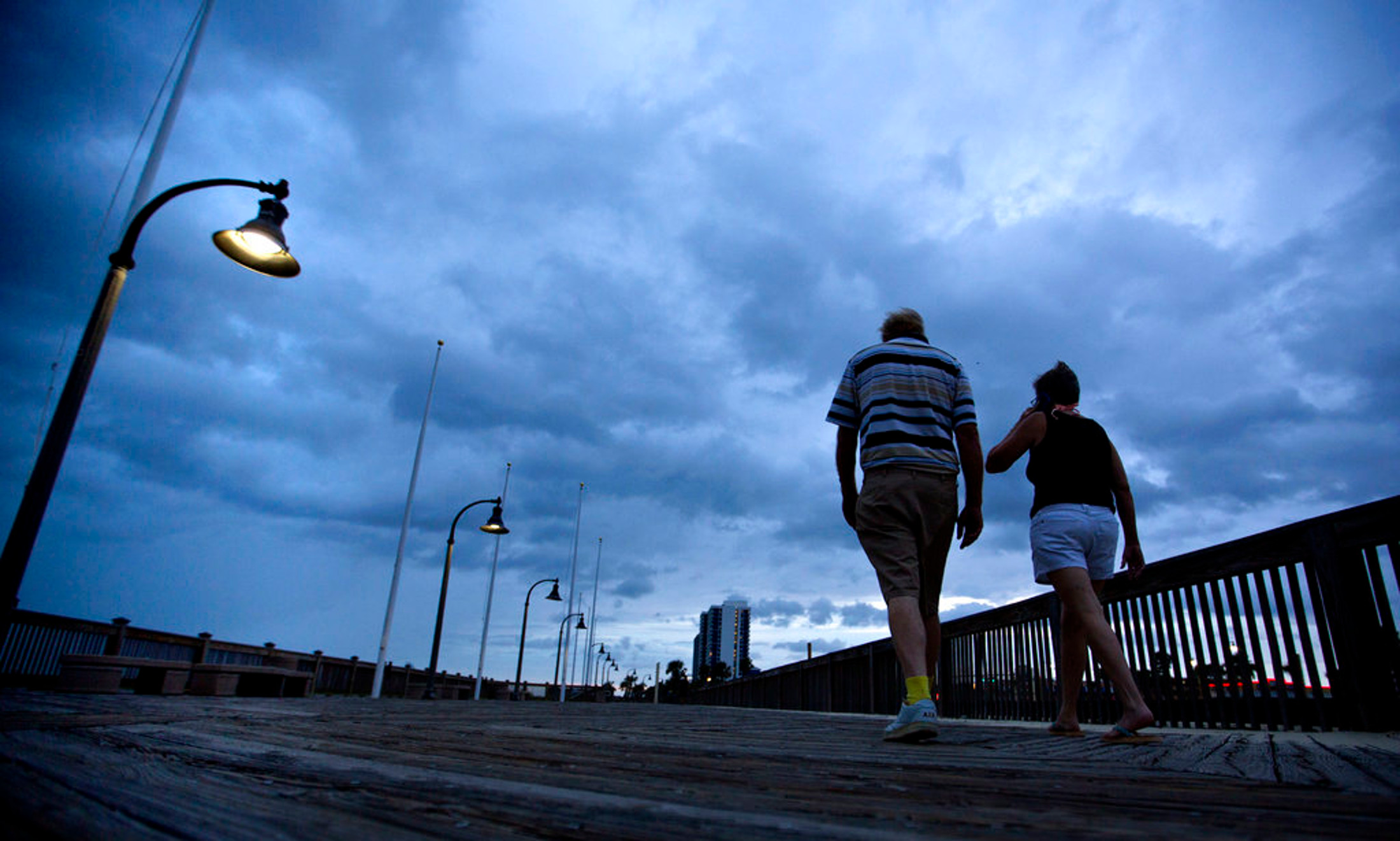 A couple walks along the boardwalk as Hurricane Florence approaches Myrtle Beach, S.C., Thursday, Sept. 13, 2018. (AP Photo/David Goldman)