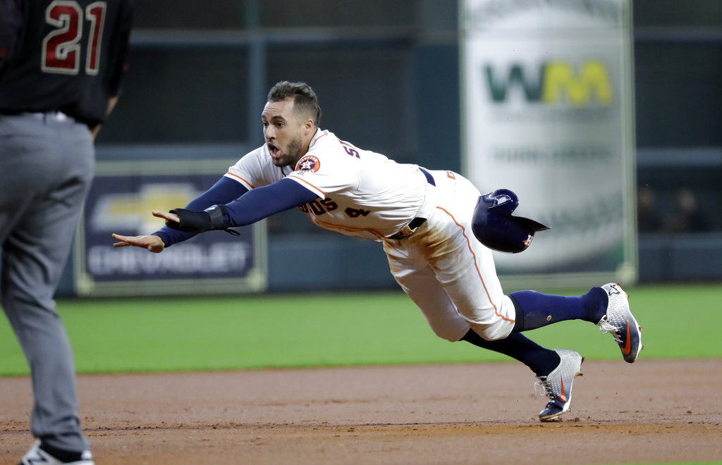 Houston Astros' George Springer (4) dives safely toward third base during the first inning of baseball game against the Arizona Diamondbacks Sunday, Sept. 16, 2018, in Houston. (AP Photo/David J. Phillip)