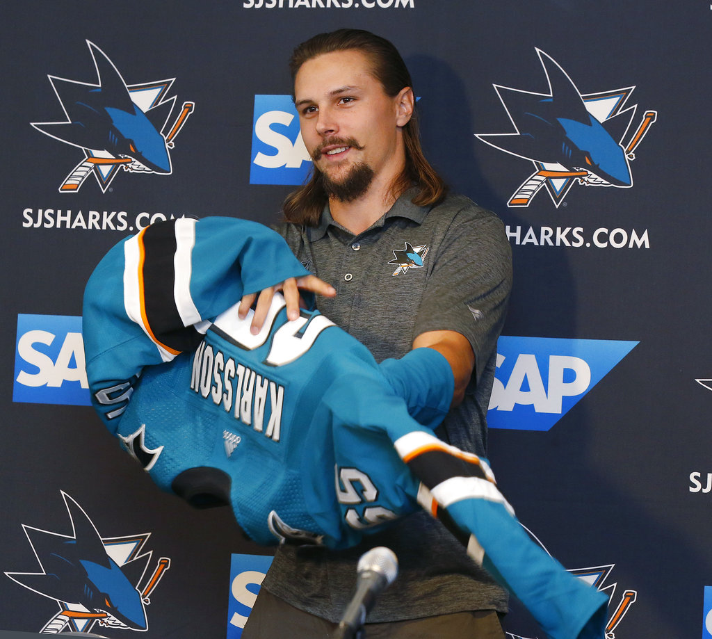 Newly acquired San Jose Sharks defenseman Erik Karlsson puts on jersey during a news conference held by the NHL hockey team in San Jose, Calif., Wednesday, Sept. 19, 2018. (AP Photo/Josie Lepe)