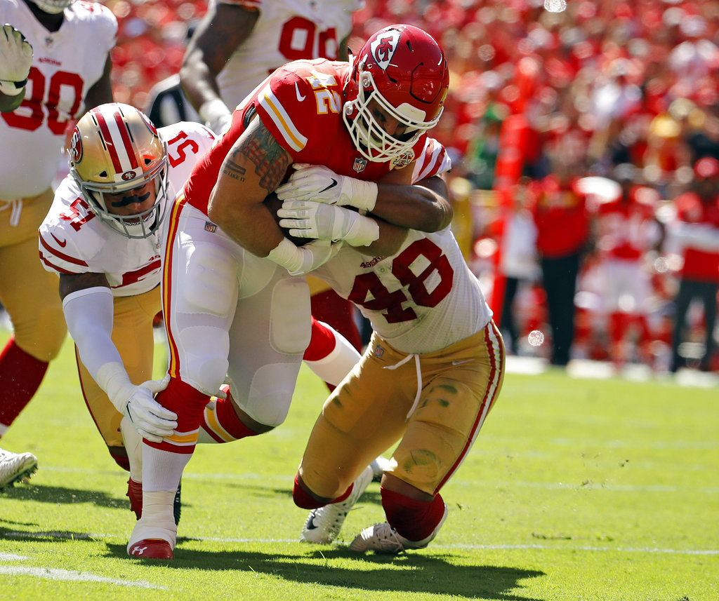 Kansas City Chiefs fullback Anthony Sherman (42) runs against a tackle by San Francisco 49ers linebackers Malcolm Smith (51) and Fred Warner (48) during the first half of an NFL football game in Kansas City, Mo., Sunday, Sept. 23, 2018. (AP Photo/Charlie Riedel)