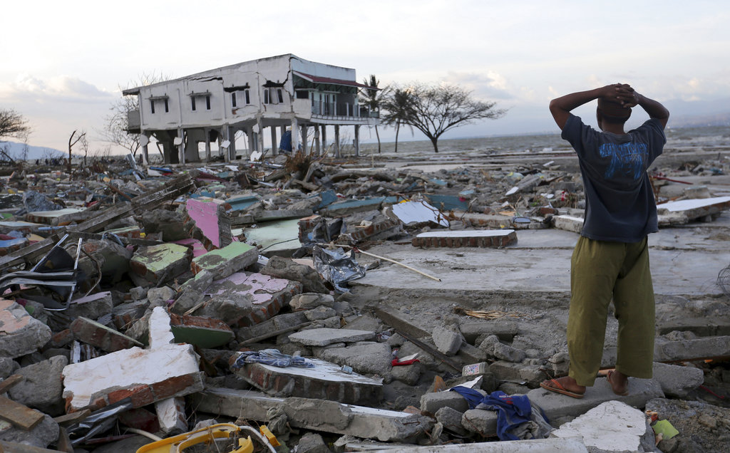 In this Saturday, Oct. 6, 2018, file photo, a villager stands amidst destruction caused by an earthquake and tsunami in Palu, Central Sulawesi, Indonesia. (AP Photo/Tatan Syuflana, File)