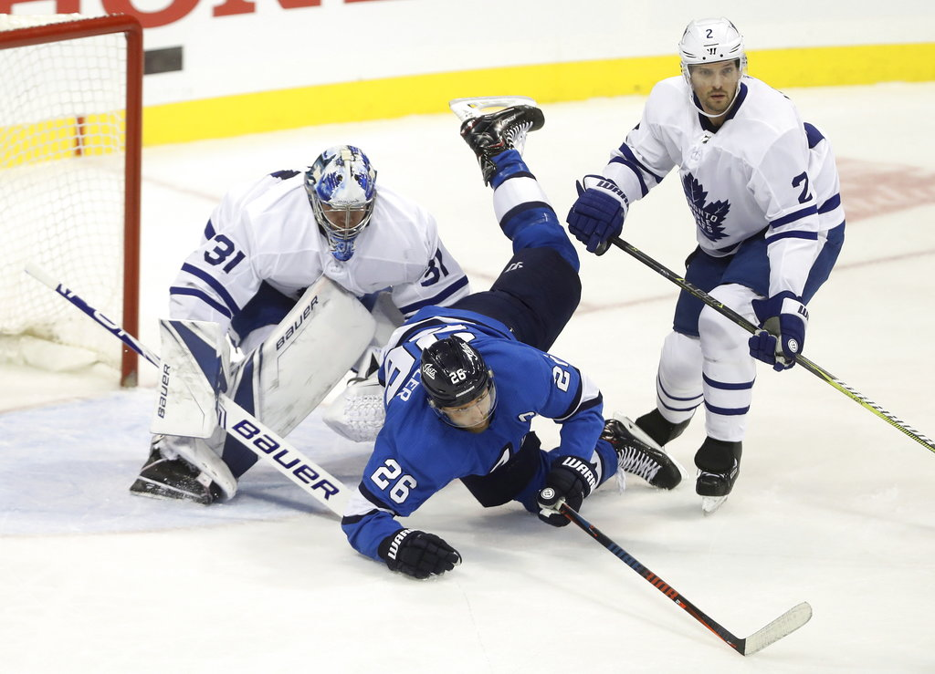 Winnipeg Jets' Blake Wheeler (26) crashes over Toronto Maple Leafs goaltender Frederik Andersen (31) after colliding with Ron Hainsey (2) during first period NHL hockey action in Winnipeg, Manitoba, Wednesday, Oct. 24, 2018. (Trevor Hagan/The Canadian Press via AP)