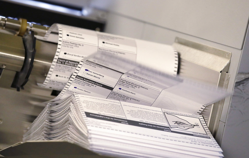 Ballots flip out of a machine scanning them at the King County Elections office Monday, Nov. 5, 2018, in Renton, Wash. The new machine can scan up to 17,000 ballots an hour, considerably more than machines previously used there that could, at best, scan 1,200 ballots in an hour. (AP Photo/Elaine Thompson)