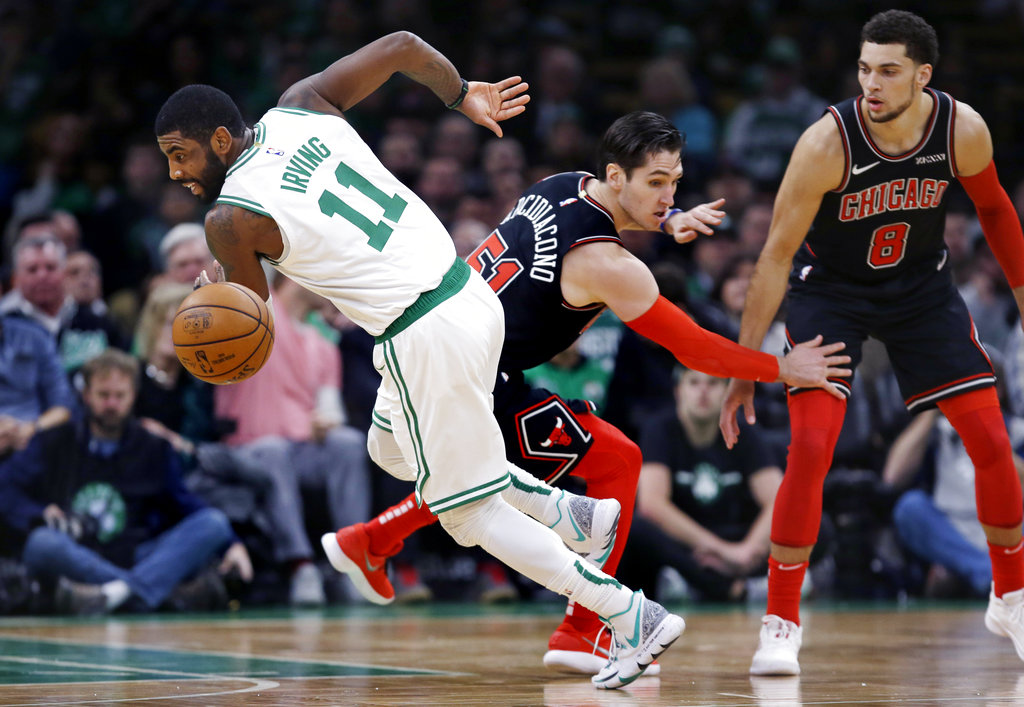 Boston Celtics guard Kyrie Irving (11) fakes out Chicago Bulls guard Ryan Arcidiacono (51) as he dribbles behind his back on a drive to the basket during the first quarter of an NBA basketball game in Boston, Wednesday, Nov. 14, 2018. (AP Photo/Charles Krupa)