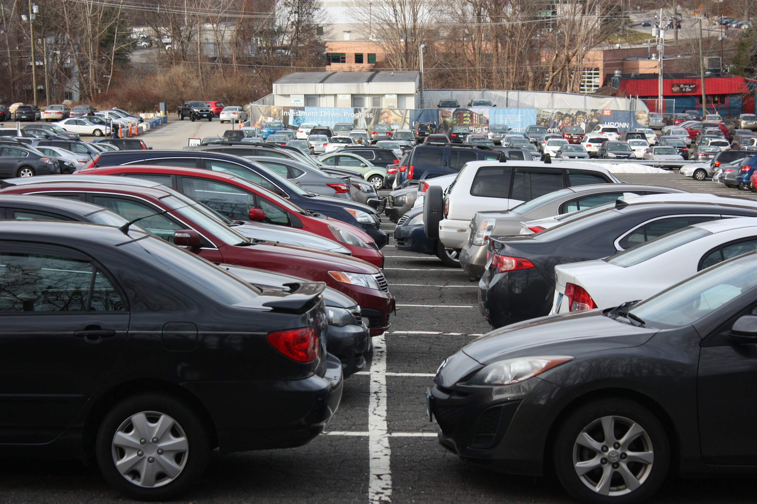 A full lot of cars in the X parking lot on the North side of UConn's Storrs campus on December 5, 2018. Students are questioning the legality of advertisements being placed on cars in UConn parking lots. (Judah Shingleton/The Daily Campus)