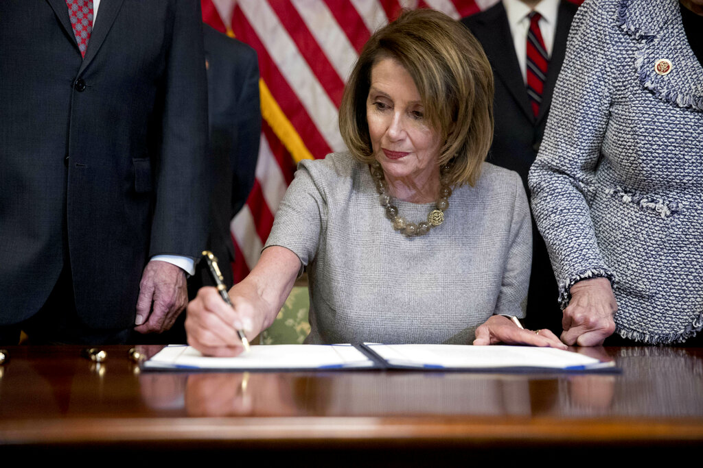 House Speaker Nancy Pelosi of Calif., signs a funding deal to reopen the government on Capitol Hill in Washington, Friday, Jan. 25, 2019. The measure now goes to the White House for President Donald Trump to sign. (AP Photo/Andrew Harnik)
