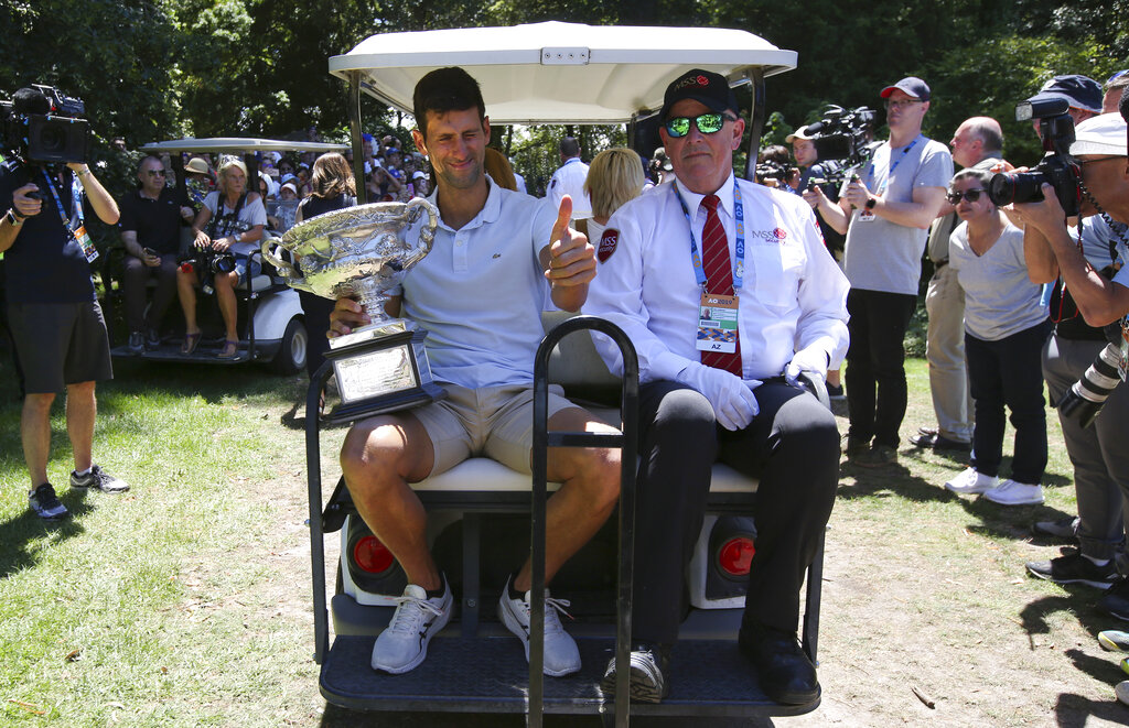 Serbia's Novak Djokovic gestures as he rides with his trophy, the Norman Brookes Challenge Cup, at Melbourne's Royal Botanic Gardens following his win over Rafael Nadal of Spain in the men's singles final at the Australian Open tennis championships in Melbourne, Australia, Monday, Jan. 28, 2019. (AP Photo/Aaron Favila)