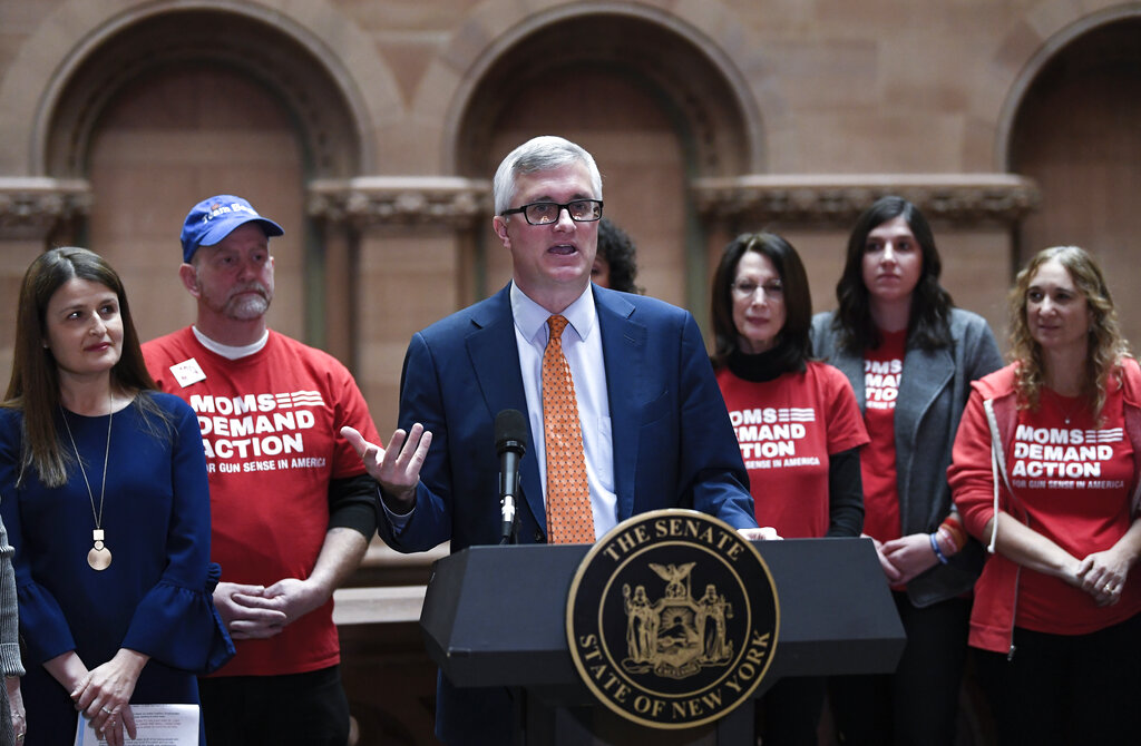 Sen. Brian Kavanagh, D-Manhattan, stands with gun control advocates during a news conference after a Senate session announcing legislation reforms to protect New Yorkers from gun violence in the at the state Capitol on Tuesday, Jan. 29, 2019, in Albany, N.Y. (AP Photo/Hans Pennink)