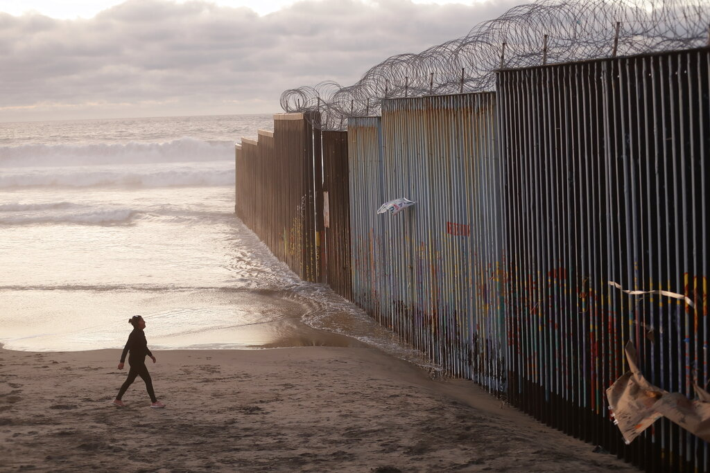 FILE - In this Jan. 9, 2019 file photo, a woman walks on the beach next to the border wall topped with razor wire in Tijuana, Mexico. A group of former U.S. national security officials is set to release a statement on Monday, Feb. 25, arguing that there is no justification for President Donald Trump to use a national emergency declaration to fund a wall along the U.S.-Mexico border. (AP Photo/Gregory Bull, File)