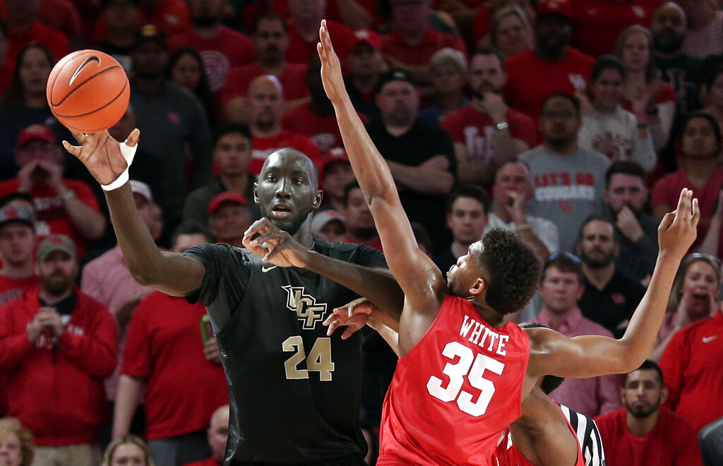 Central Florida center Tacko Fall (24) passes the ball as Houston forward Fabian White Jr. (35) defends during the second half of an NCAA college basketball game Saturday, March 2, 2019, in Houston. (AP Photo/Michael Wyke)