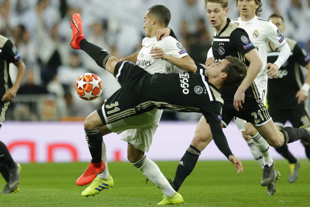 Real forward Lucas Vazquez, background, and Ajax's Nicolas Tagliafico challenge for the ball during the Champions League soccer match between Real Madrid and Ajax at the Santiago Bernabeu stadium in Madrid, Spain, Tuesday, March 5, 2019. (AP Photo/Manu Fernandez)