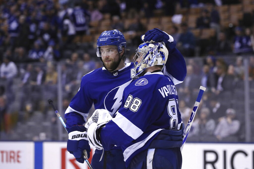 Tampa Bay Lightning defenseman Victor Hedman (77) celebrates with goaltender Andrei Vasilevskiy (88) after their victory over the Toronto Maple Leafs in NHL hockey game action in Toronto on Monday, March 11, 2019. (Cole Burston/The Canadian Press via AP)