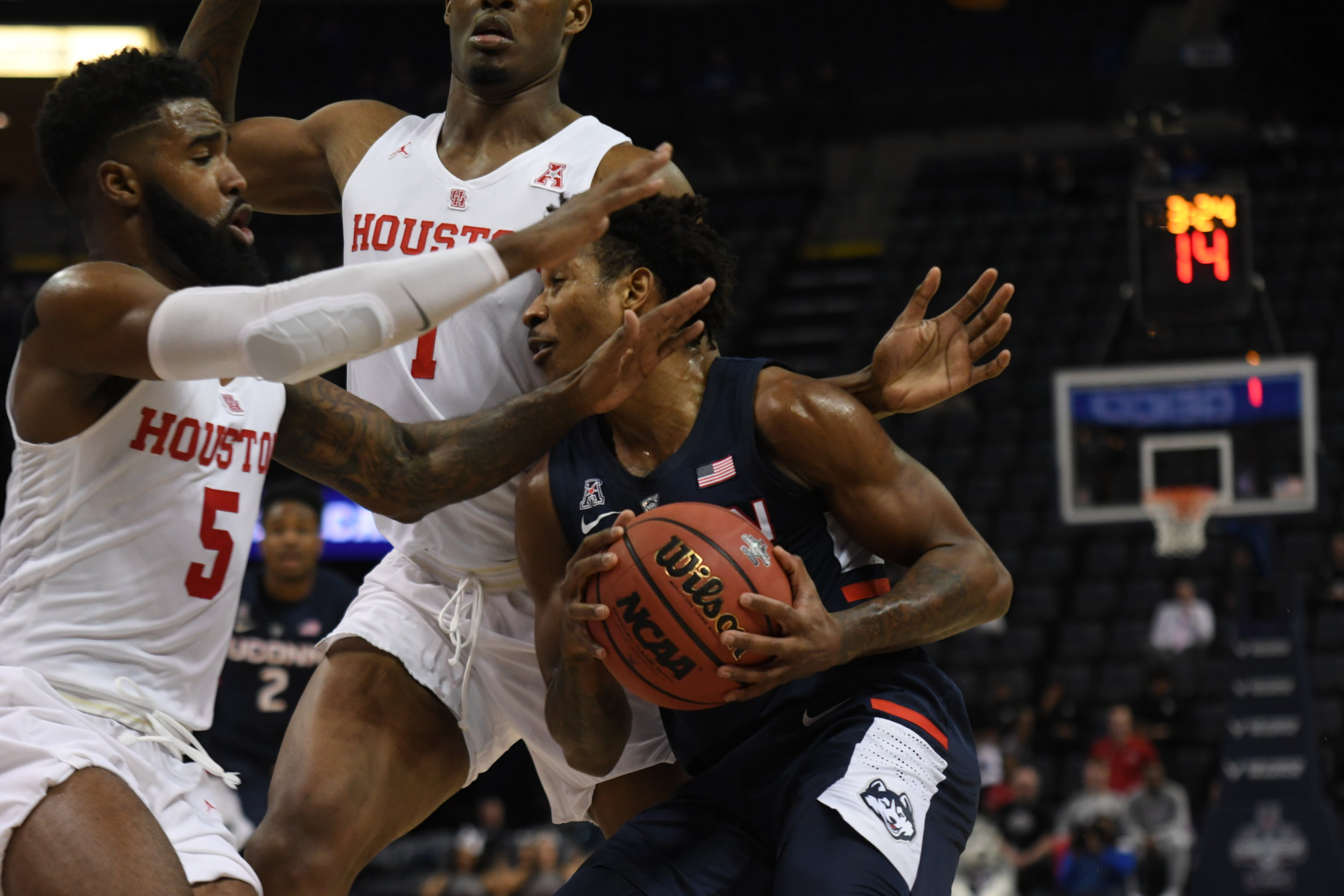 Christian Vital plows through two Houston defenders in UConn's 85-45 loss to Houston in the quarterfinals of the American Athletic Conference Tournament on Friday, March 15 in Memphis, Tenn. (Judah Shingleton/The Daily Campus)
