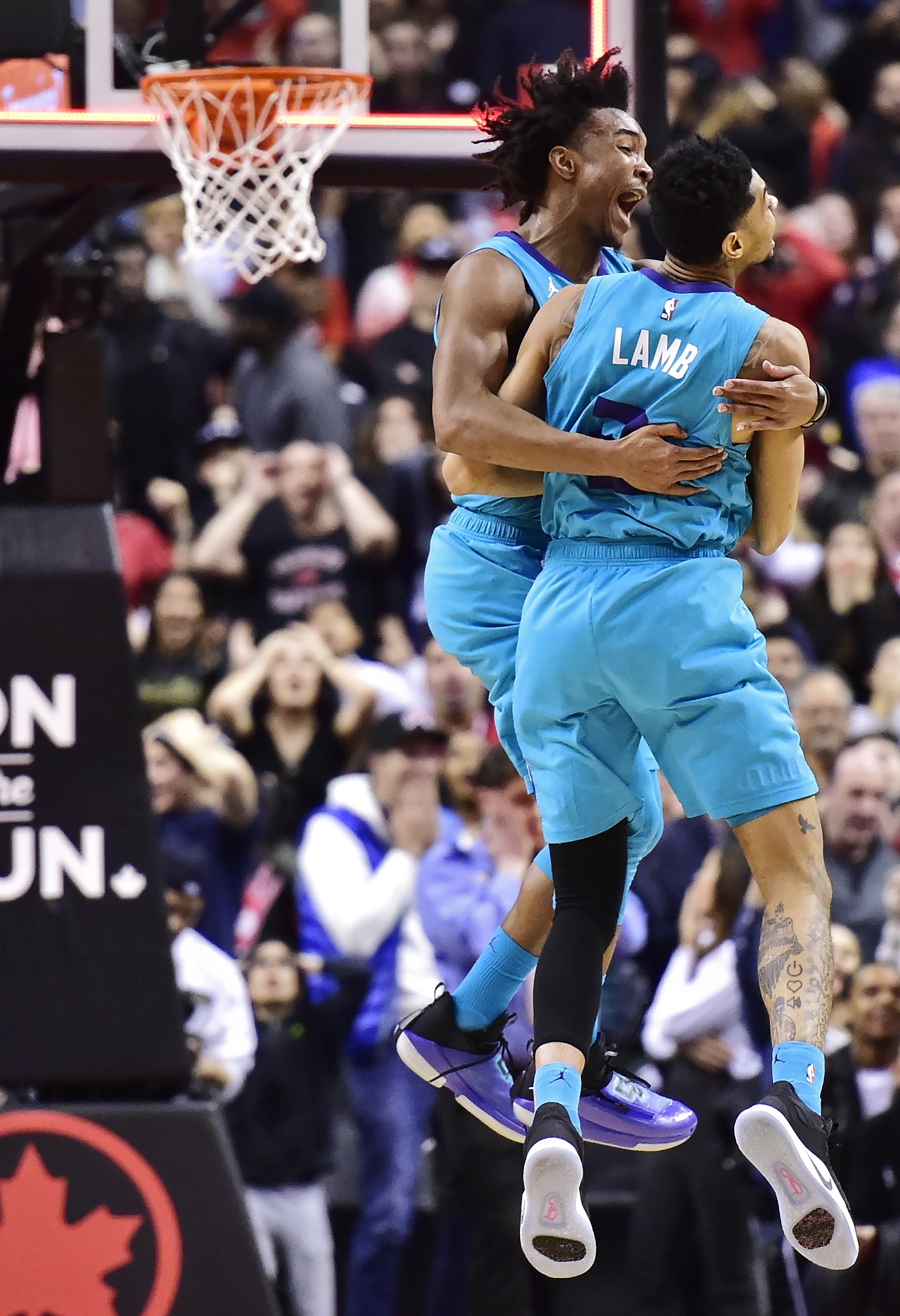 Charlotte Hornets guard Jeremy Lamb (3) celebrates his game-winning basket against the Toronto Raptors with teammate Devonte' Graham, left, in an NBA basketball game Sunday, March 24, 2019, in Toronto. (Frank Gunn/The Canadian Press via AP)