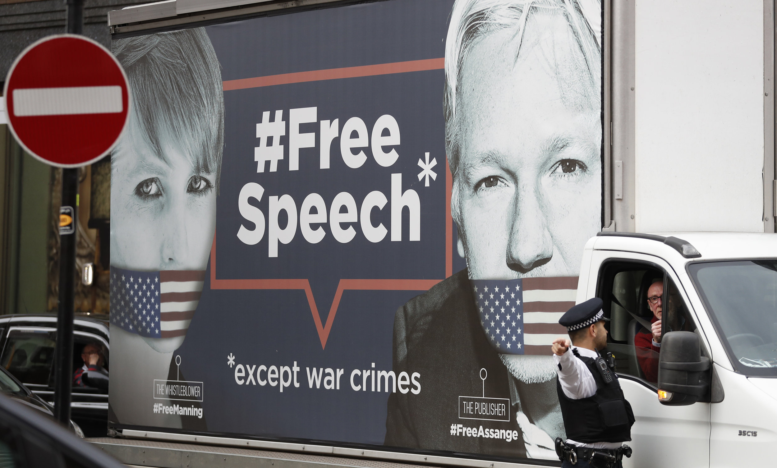 "A policeman directs a van with a 'Free Speech' placard and the images of Wikileaks founder Julian Assange and whistleblower Chelsea Manning on its side, near the Ecuadorian Embassy, in London, Friday, April 5, 2019. Assange has been hold out since in the embassy since 2012. A senior Ecuadorian official said no decision has been made to expel Julian Assange from the country's London embassy despite tweets from Wikileaks that sources had told it he could be kicked out within ""hours to days"" on Friday. (AP Photo/Alastair Grant)"