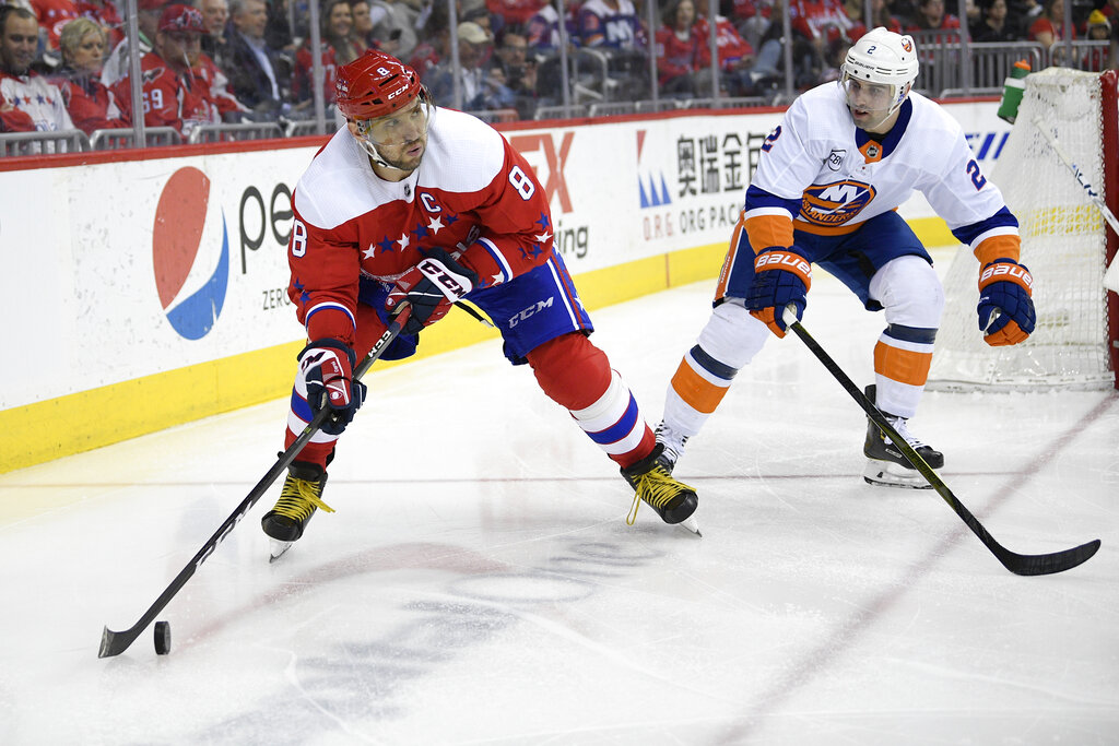 Washington Capitals left wing Alex Ovechkin (8), of Russia, skates with the puck against New York Islanders defenseman Nick Leddy (2) during the second period of an NHL hockey game, Saturday, April 6, 2019, in Washington. (AP Photo/Nick Wass)