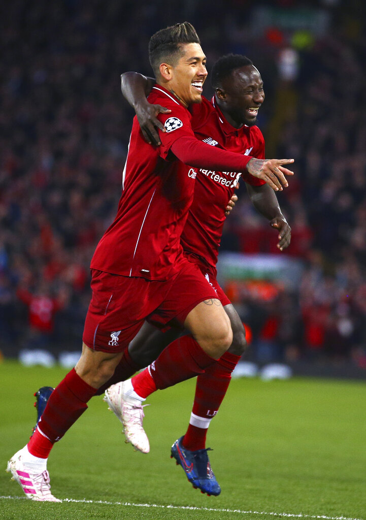 Liverpool's Naby Keita celebrates with Roberto Firmino, left, after scoring the opening goal during the Champions League quarterfinal, first leg, soccer match between Liverpool and FC Porto at Anfield Stadium, Liverpool, England, Tuesday April 9, 2019. (AP Photo/Dave Thompson)