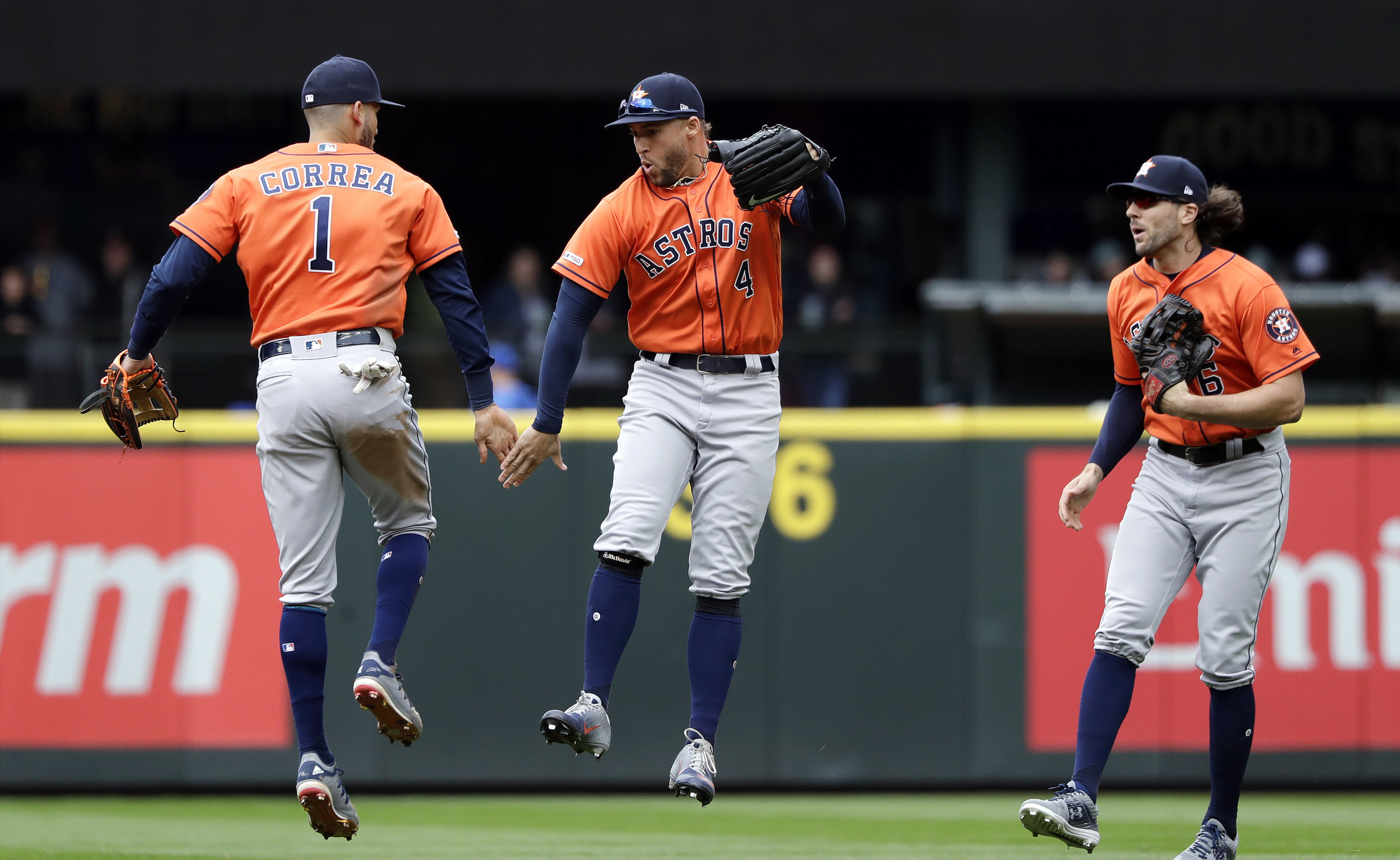 Houston Astros' Carlos Correa (1), George Springer (4), and Jake Marisnick celebrate after the team beat the Seattle Mariners in a baseball game Sunday, April 14, 2019, in Seattle. The Astros won 3-2. (AP Photo/Elaine Thompson)
